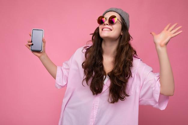 Pozytywna uśmiechnięta szczęśliwa atrakcyjna młoda brunetka kobieta ubrana w szary kapelusz stylowy różowy koszula i
