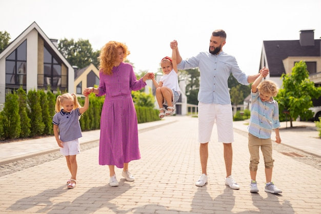 Pozytywna wesoła rodzina, trzymając się za ręce
