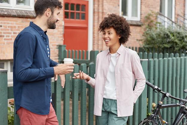 Pozytywna wielorasowa para spaceruje po wiejskim otoczeniu, spaceruje w weekendy, pije kawę na wynos, stoi przy ogrodzeniu, przyjemnie rozmawia ze sobą