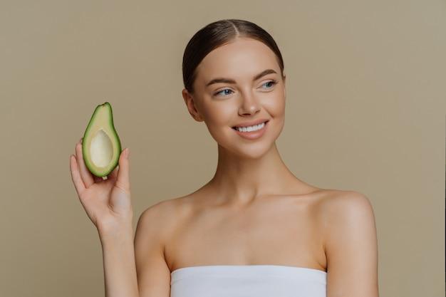 Pozytywna, zdrowa, zadowolona kobieta czule patrzy w bok, uśmiecha się delikatnie trzyma połowę awokado