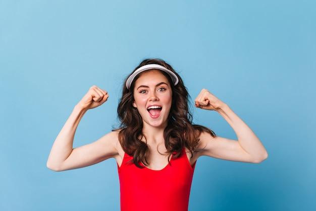 Pozytywna zielonooka kobieta w czapce demonstruje siłę swoich dłoni