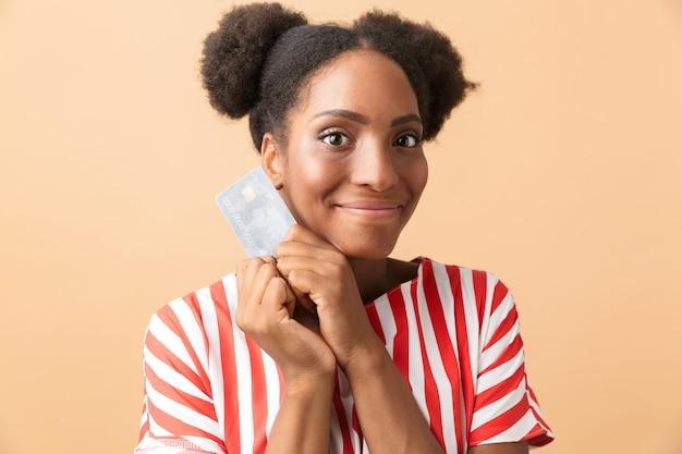 Pozytywne african american kobieta uśmiecha się i trzyma kartę kredytową, na białym tle