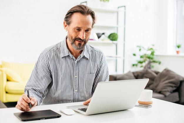 Pozytywne brodaty kaukaski mężczyzna siedzi przed swoim laptopem i uśmiecha się trzymając rysik na tablecie graficznym