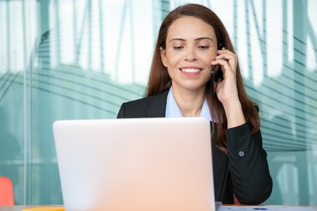 Pozytywne całkiem młoda bizneswoman rozmawia przez telefon komórkowy i uśmiecha się, pracując przy komputerze w biurze, używając laptopa przy stole