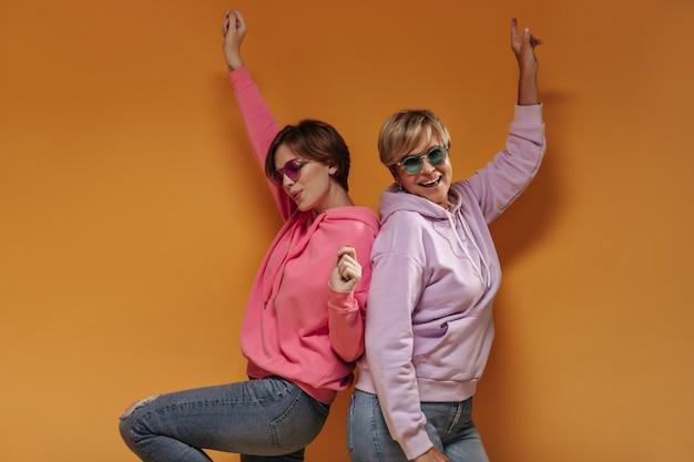 Pozytywne dwie panie z nowoczesnymi krótkimi fryzurami w fajnych okularach przeciwsłonecznych i szerokich różowych bluzach z kapturem, dobrze się bawiąc na pomarańczowym tle.
