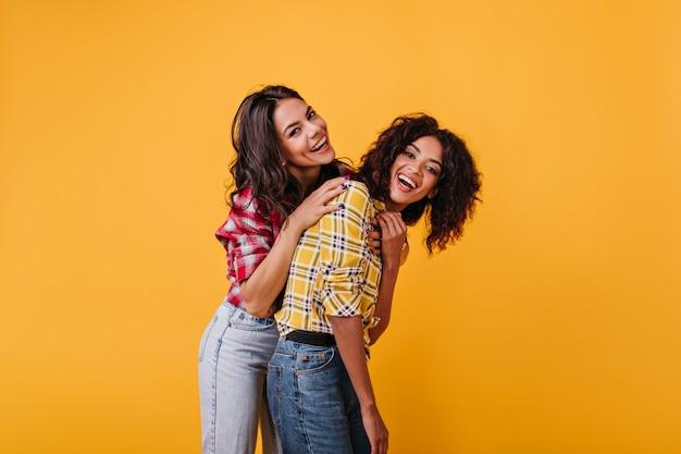 Pozytywne dziewczyny relaksują się i bawią podczas sesji zdjęciowej w żółtym pokoju. portret śmiejących się opalonych dziewcząt z kręconymi włosami.