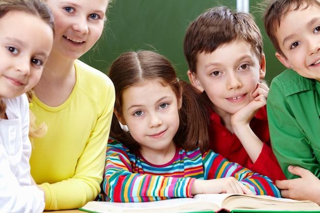 Pozytywne elementarne studenci z książką w klasie
