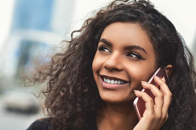 Pozytywne emocje. koncepcja stylu życia. zamknij się młoda kobieta rasy mieszanej za pomocą telefonu.