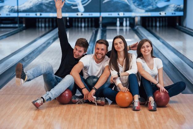 Pozytywne emocje. młodzi weseli przyjaciele bawią się w kręgle w weekendy