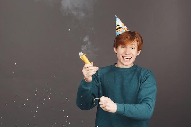 Pozytywne emocje. portret młodego rudowłosego faceta w zielony sweter zabawy na przyjęciu urodzinowym z rodziną