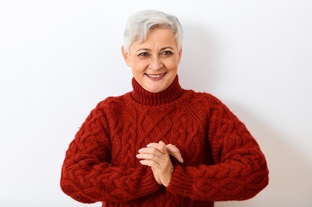 Pozytywne emocje, reakcja i uczucia. portret atrakcyjnej wesołej starszej pani z krótką szarą fryzurą, która wybuchnie śmiechem, jest w dobrym nastroju, trzymając się za ręce w namaste