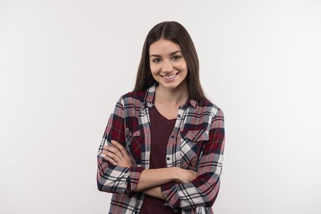 Pozytywne emocje. szczęśliwa młoda kobieta uśmiecha się do ciebie, stojąc z rękami skrzyżowanymi