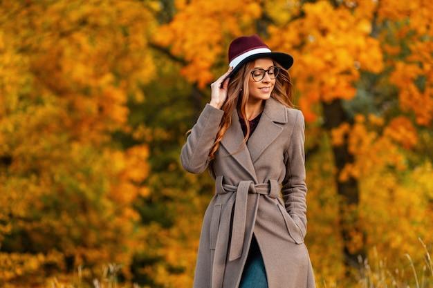 Pozytywne hipster młoda kobieta w modnej odzieży wierzchniej w eleganckim kapeluszu w stylowych okularach spacery po parku. radosna dziewczyna z uroczym uśmiechem cieszy się weekendem. jesienna kolekcja odzieży damskiej.