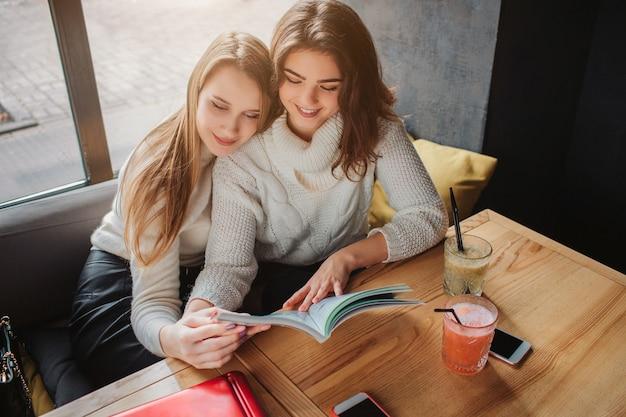 Pozytywne i miłe młode kobiety siedzą przy stole i patrzą na dziennik. uśmiechają się. dziewczyny siedzą i obejmują się.