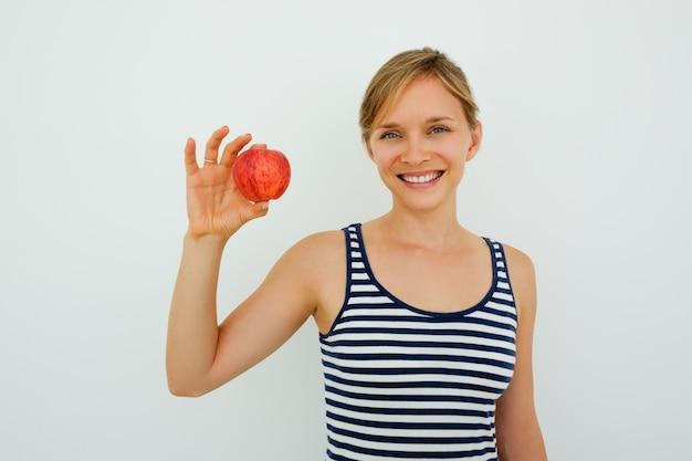 Pozytywne kobiety z zdrowych zębów wykazujące jabłko