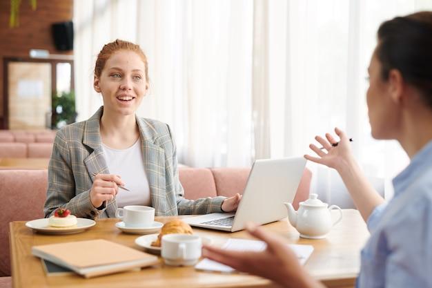 Pozytywne kreatywne młode panie biznesu siedzą przy stole w przytulnej kawiarni i gestykulują rękami podczas burzy mózgów na temat projektu na spotkaniu