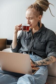 Pozytywne ładna młoda dziewczyna z dredami i piercing w pomieszczeniu przy użyciu komputera przenośnego picia herbaty.