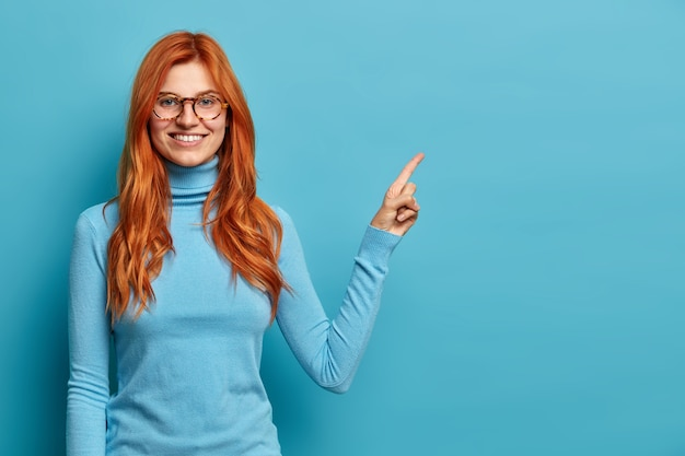 Pozytywne ładne wyglądające rudowłosy caucasion kobieta z toothy uśmiech punktów na przestrzeni kopii w prawym górnym rogu.