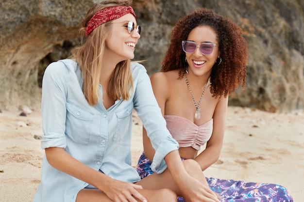 Pozytywne lesbijki bawią się razem na gorącej słonecznej plaży, śmieją się z czegoś zabawnego, są innej rasy. szczęśliwe feministki cieszą się wakacjami i byciem razem