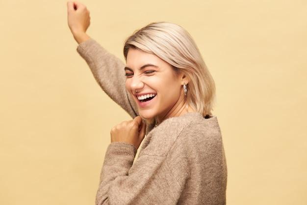 Pozytywne ludzkie emocje i uczucia. radosna szczęśliwa młoda kobieta z fryzurą bob i kolczykiem w nosie świętuje sukces, śmieje się i tańczy, ma wesoły wyraz twarzy, pozowanie na białym tle
