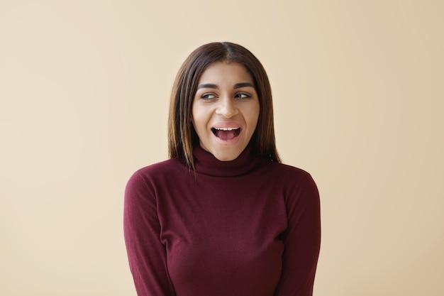 Pozytywne ludzkie emocje i uczucia. zdjęcie emocjonalnej młodej kobiety rasy mieszanej, patrzącej z ukosa z podekscytowanym wyrazem twarzy, szeroko otwierającej usta