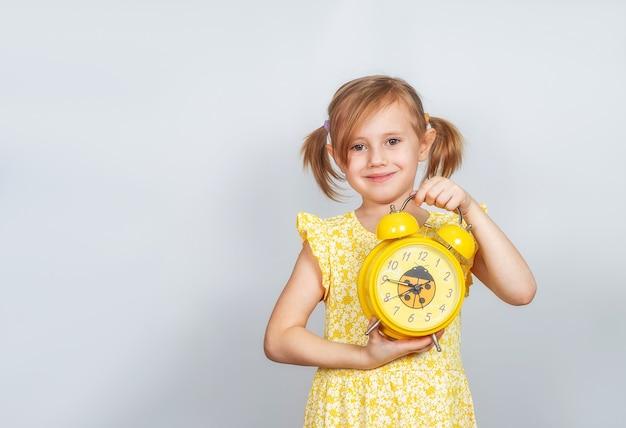 Pozytywne mała dziewczynka kaukaska trzyma w ręku budzik i uśmiecha się