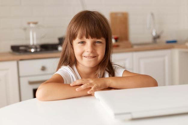 Pozytywne małe ciemnowłose dziecko płci żeńskiej siedzi przy stole w pobliżu złożonego laptopa, patrząc na kamerę z przyjemnym wyrazem twarzy, pozowanie w domu w kuchni.