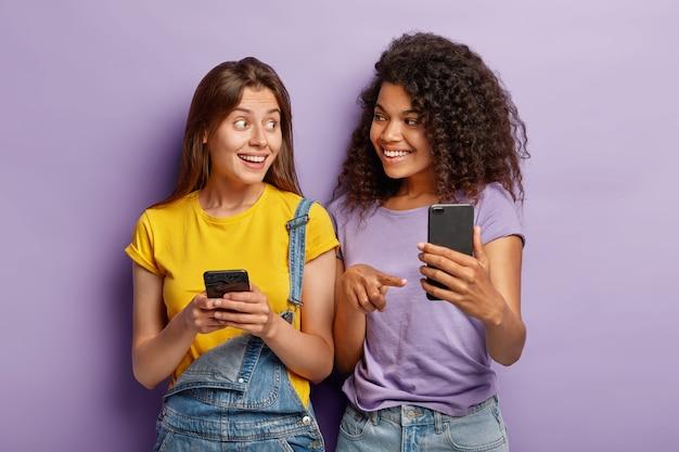 Pozytywne milenialsi siostry rasy mieszanej pozują z nowoczesnymi smartfonami, uzależnione od technologii, czatują online