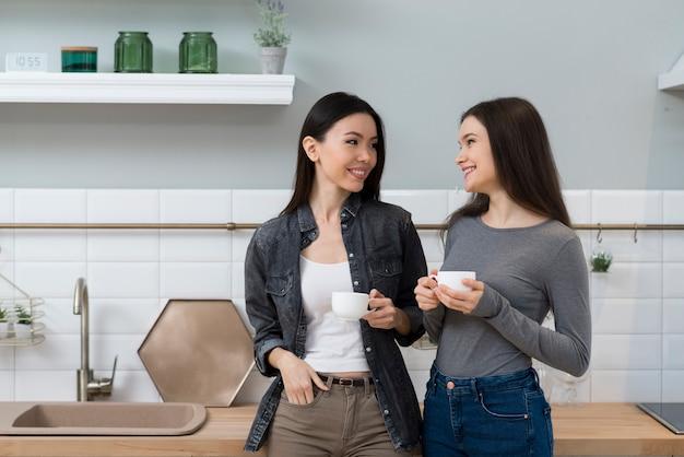 Pozytywne młode kobiety ma kawę wpólnie