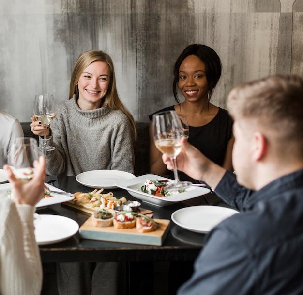 Pozytywne młode kobiety ono uśmiecha się przy obiadowym przyjęciem