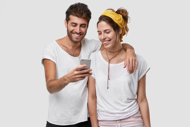 Pozytywne młode małżeństwo obejmuje się, radośnie patrzy na telefon komórkowy, chętnie ogląda wspólne zdjęcia