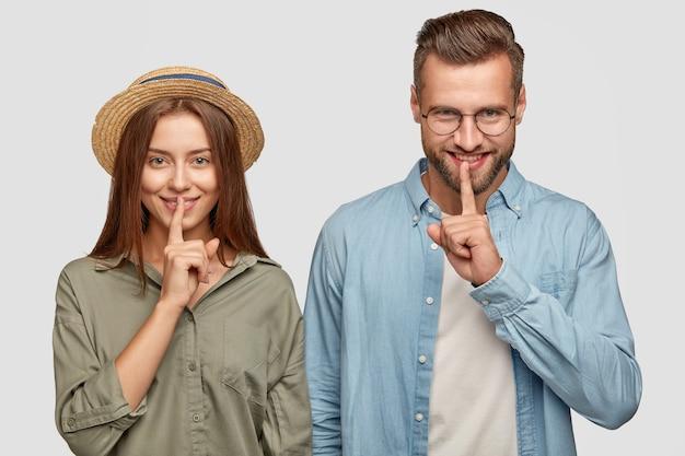Pozytywne młode nastolatki dzielą się plotkami i plotkami, trzymają palce wskazujące na ustach