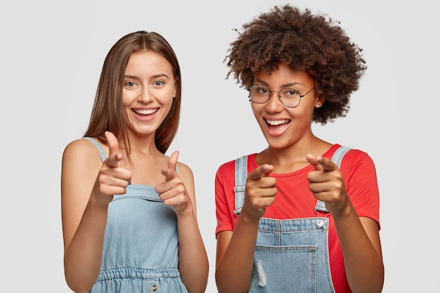 Pozytywne, mutliethinic młode kobiety wskazują obiema palcami wskazującymi
