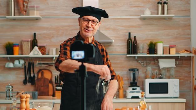Pozytywne nagranie kucharza w kuchni nowego przepisu na kanał wideo. emerytowany bloger piekarz influencer wykorzystujący technologię internetową do komunikacji, strzelania, blogowania w mediach społecznościowych za pomocą sprzętu cyfrowego