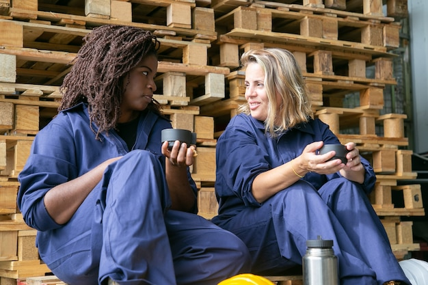 Pozytywne pracownice fabryki rozmawiają przy kawie, siedząc na drewnianych platformach w magazynie