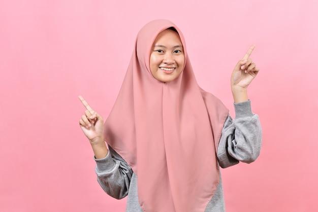 Pozytywne punkty powyżej, przedstawiające azjatki, muzułmanki, pokazują miejsce na twój tekst reklamowy. uśmiecha się przyjemnie ubrana w hidżab na białym tle na różowym tle. świetny pomysł fajna oferta
