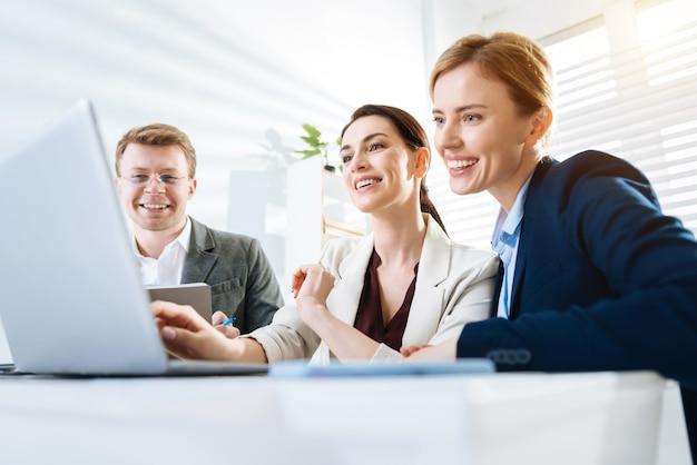 Pozytywne rezultaty. trzej radośnie optymistyczni koledzy patrzą na ekran, śmiejąc się i czując zadowolenie z pracy