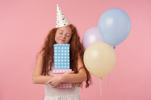 Pozytywne rude kręcone dziecko kobiece pozuje na różowym tle studia z kolorowymi balonami, trzyma pudełka z prezentami z zamkniętymi oczami i uśmiecha się radośnie, nosi świąteczne ubrania i czapkę urodzinową