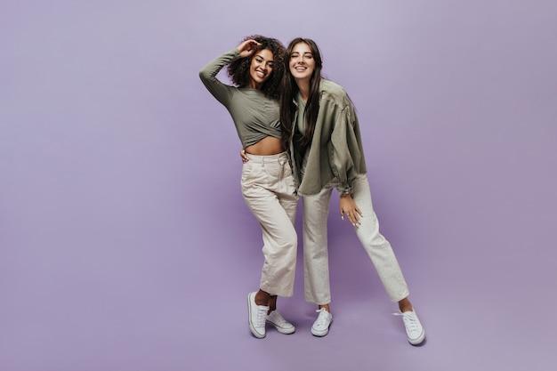 Pozytywne stylowe dziewczyny z brunetkową fryzurą w beżowych fajnych spodniach, białych tenisówkach i oliwkowych koszulach uśmiechają się i patrzą w kamerę