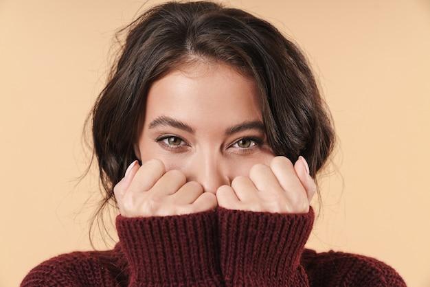 Pozytywne szczęśliwa młoda brunetka kobieta pozowanie na białym tle nad beżową ścianą pokrywającą twarz rękami.