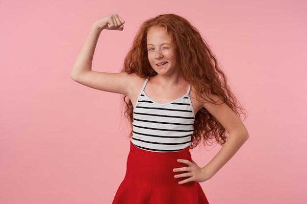 Pozytywne urocze dziecko płci żeńskiej z długimi lśniącymi włosami pozuje na różowym tle w czerwonej spódnicy i topie w paski, mruga wesoło do aparatu i podnosi rękę, by pokazać swoją moc