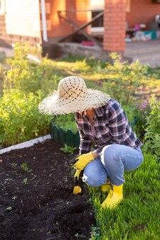 Pozytywne uśmiechnięta młoda kobieta ogrodnik sadzi rośliny w łóżku ogrodowym wiosną w ciepły słoneczny dzień. koncepcja rolnictwa ekologicznego i hobby