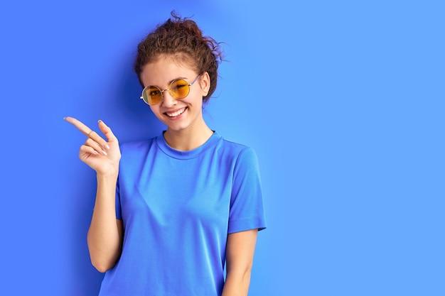 Pozytywne uśmiechnięte dziewczyny nastolatka, wskazując palcami po bokach, indeks po lewej stronie
