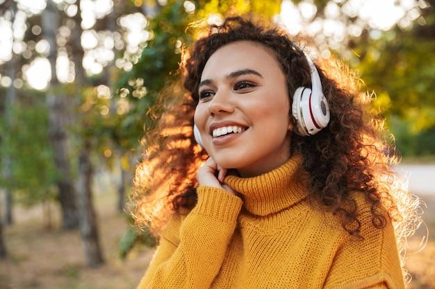 Pozytywne wesoły piękna młoda kobieta kręcone spaceru w parku na zewnątrz słuchania muzyki w słuchawkach.