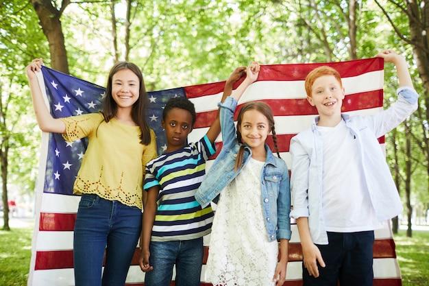 Pozytywne wieloetnicznego dzieci trzymając amerykańską flagę