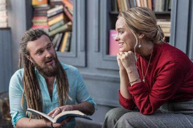 Pozytywne wieści. szczęśliwa miła kobieta patrząca na wróżkę, słuchając jego przepowiedni