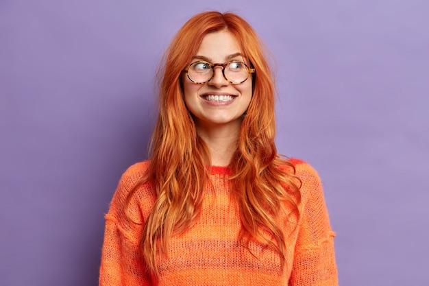 Pozytywne wyrazy twarzy. szczęśliwa uśmiechnięta kobieta z naturalnymi rudymi włosami odwraca wzrok i uśmiecha się szeroko, nosi pomarańczowy sweter w okularach.