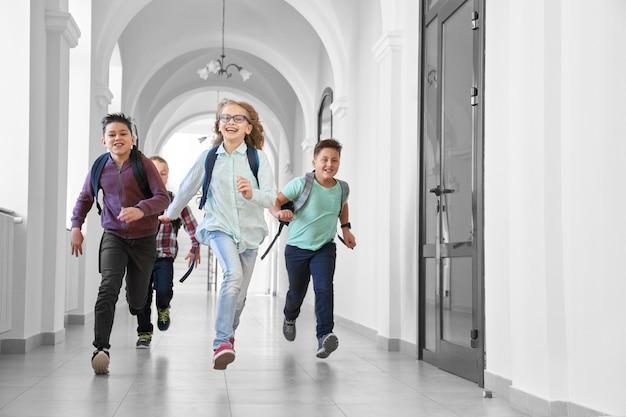 Pozytywni i szczęśliwi uczniowie szybko biegną do przodu i uśmiechają się do kamery