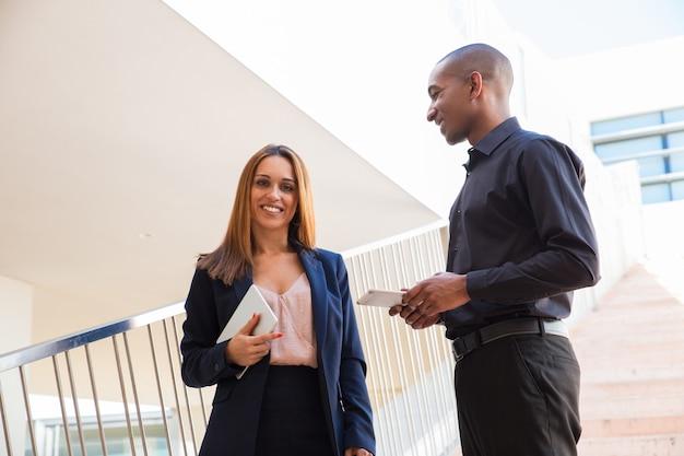 Pozytywni ludzie biznesu czatujący i trzymający tabletki na schodach