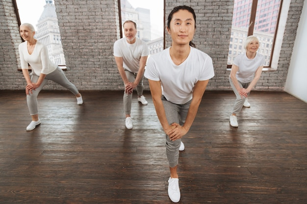 Pozytywni ludzie w strojach fitness rzucają się do przodu, zachowując uśmiech na twarzach